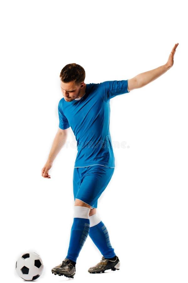 Le jeune joueur de football beau tient donner un coup de pied le ballon de football posant sur le fond d'isolement par blanc images stock
