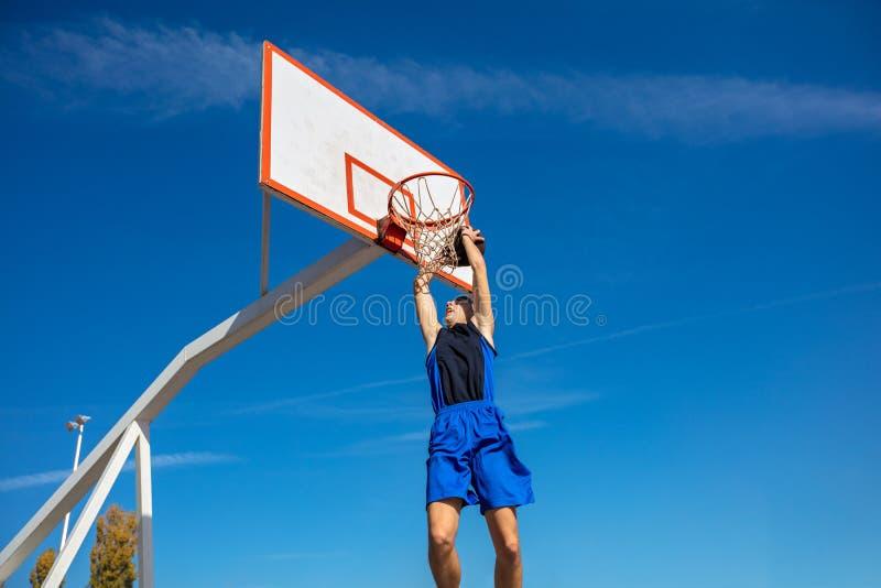 Le jeune joueur de rue de basket-ball faisant le claquement trempent images stock