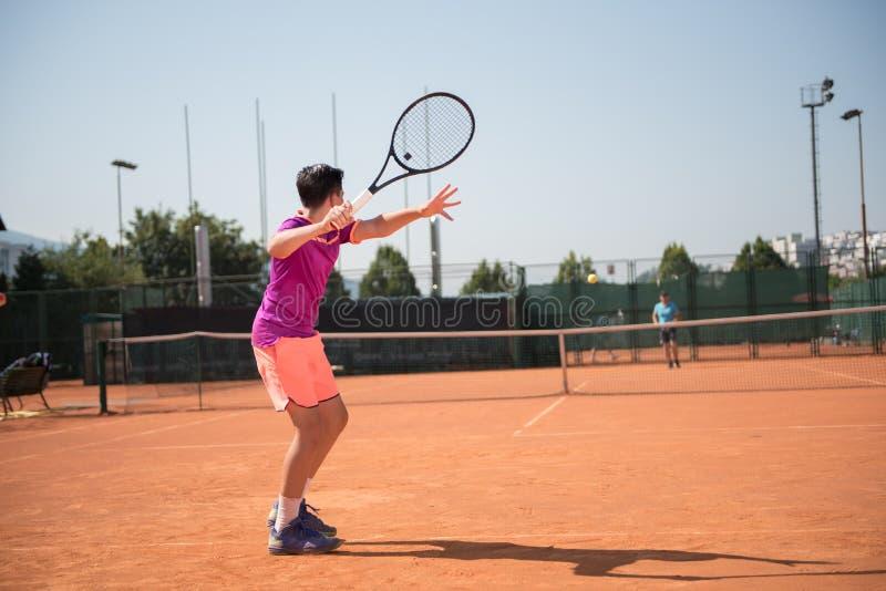 Le jeune joueur de tennis se prépare à jouer l'avant-main photo libre de droits