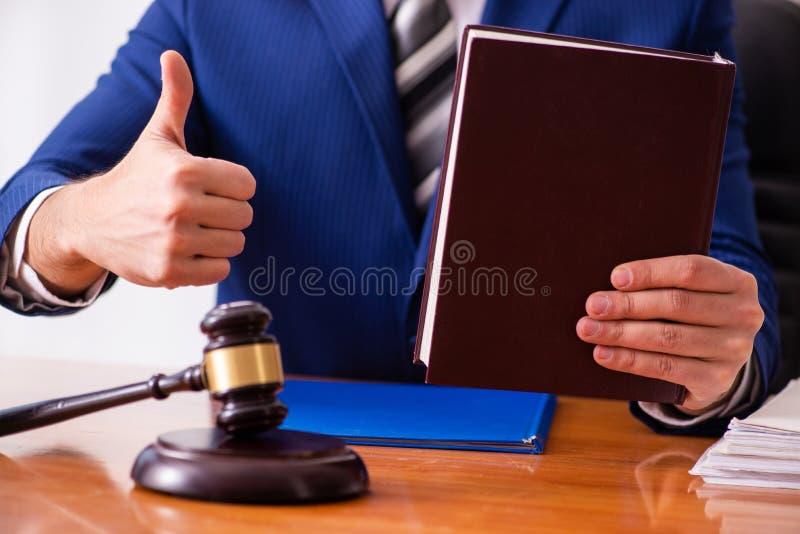 Le jeune juge masculin s'asseyant dans la salle d'audience photographie stock libre de droits