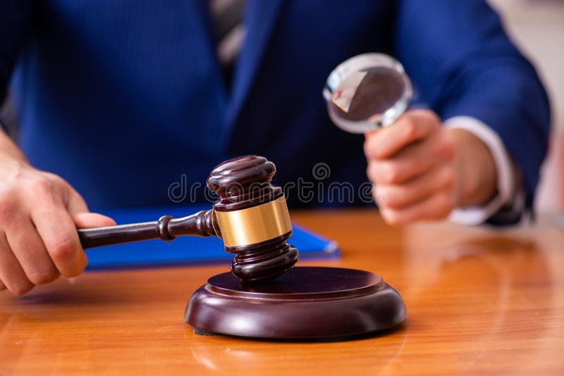 Le jeune juge masculin s'asseyant dans la salle d'audience photo stock