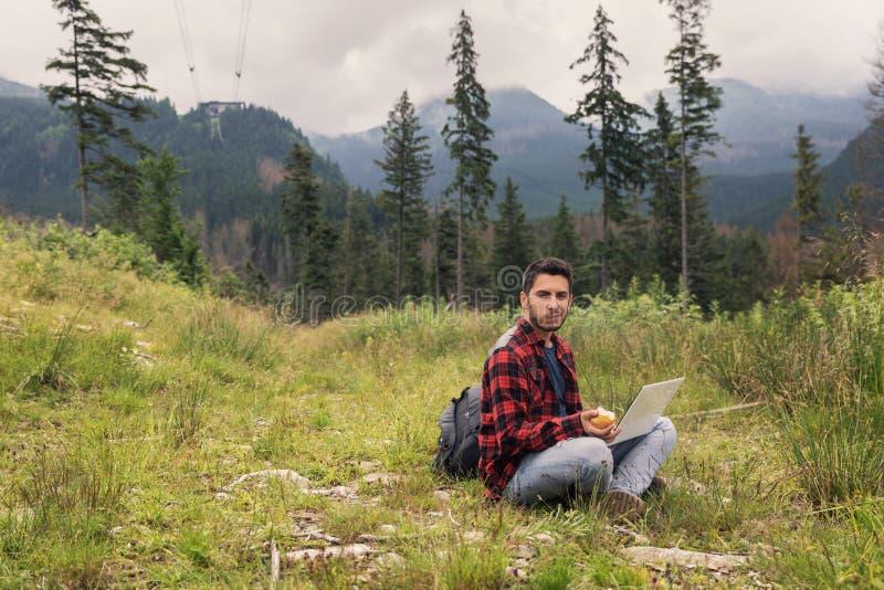 Le jeune mâle de brune dans les jeans et la chemise travaille à un ordinateur images libres de droits