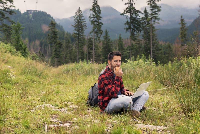 Le jeune mâle de brune dans les jeans et la chemise travaille à un ordinateur tout en étant sur la nature photographie stock