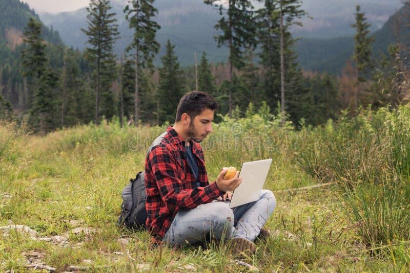 Le jeune mâle de brune dans les jeans et la chemise travaille à un ordinateur tout en étant sur la nature photos stock