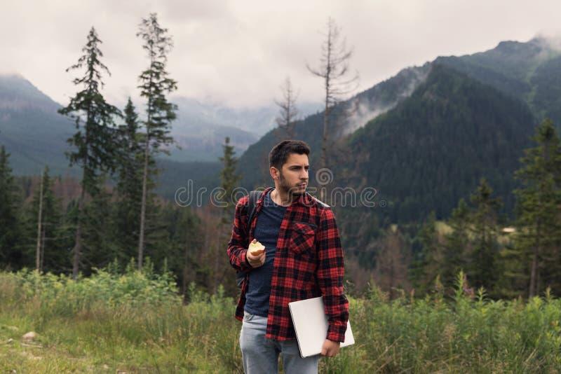 Le jeune mâle de brune dans les jeans et la chemise travaille à un ordinateur tout en étant sur la nature images stock