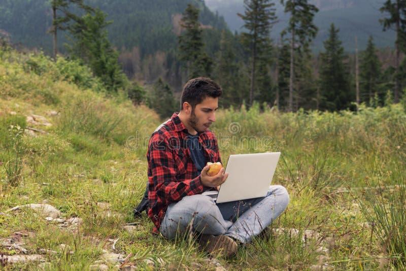 Le jeune mâle de brune dans les jeans et la chemise travaille à un ordinateur tout en étant sur la nature image stock