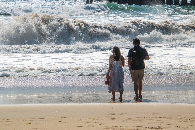 Le jeune mâle et les couples femelles sont regarder vu la mer sur la plage au bord d'un océan rugueux image libre de droits