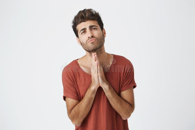 Le jeune mâle italien attirant dans le T-shirt rouge tenant des paumes a pressé ensemble devant lui avec des expressions pleines  images stock