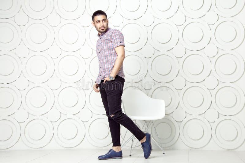 Le jeune mannequin barbu dans le style occasionnel pose près du fond blanc de mur de cercle Projectile de studio photos libres de droits