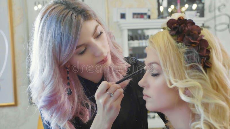 Le jeune maquilleur appliquant des cosmétiques sur le ` modèle s observe photos libres de droits