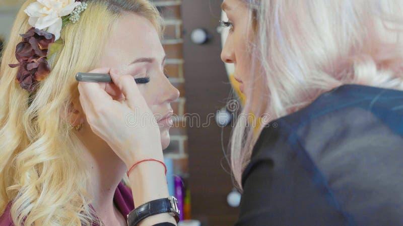 Le jeune maquilleur appliquant des cosmétiques sur le ` modèle s observe photo stock