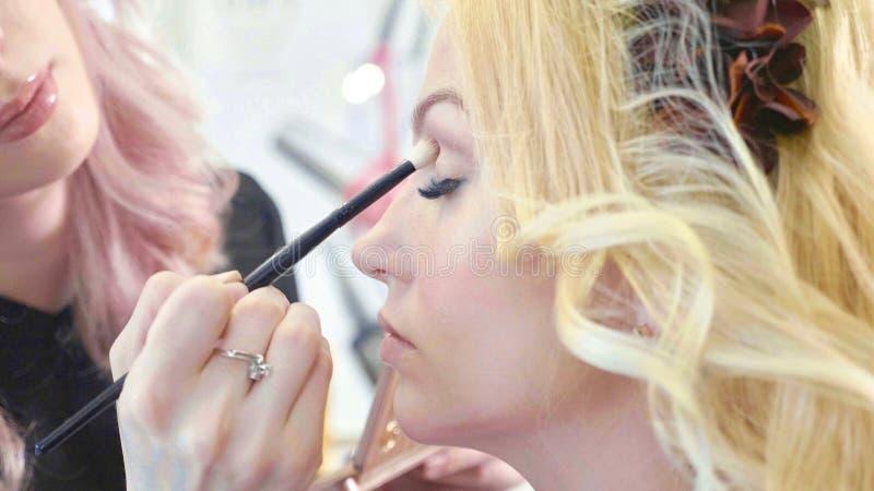 Le jeune maquilleur appliquant des cosmétiques sur le ` modèle s observe photographie stock