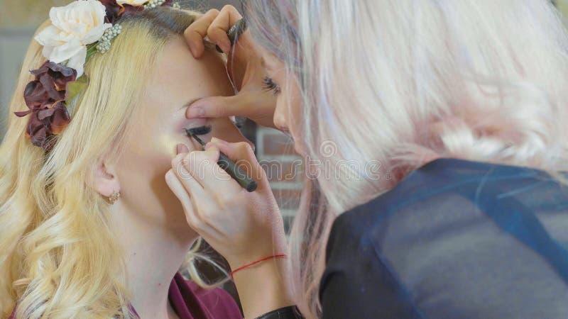 Le jeune maquilleur appliquant des cosmétiques sur le ` modèle s observe photo libre de droits