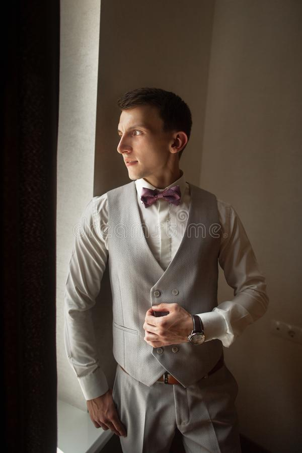 Le jeune marié à la mode attend la jeune mariée près de la fenêtre Portrait du marié dans un gilet gris photographie stock libre de droits