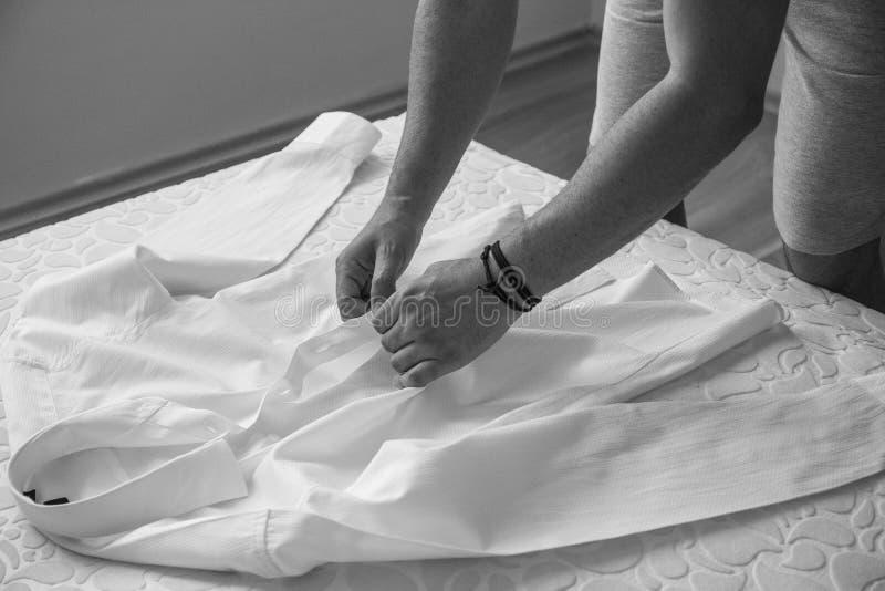 Le jeune marié a installé sa chemise blanche pour le mariage en noir et blanc photographie stock libre de droits