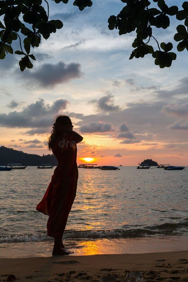 Le jeune modèle femelle dans la robe blanche et les lunettes de soleil brunes apprécie les derniers rayons du soleil photo libre de droits