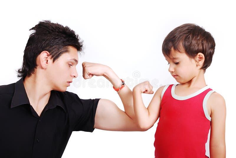 Le jeune modèle mâle affiche des muscles au petit garçon photographie stock