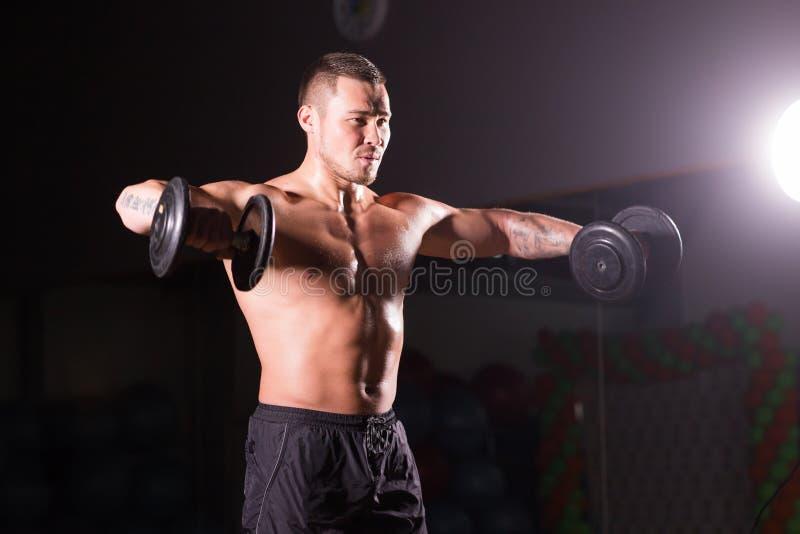 Le jeune modèle masculin sans chemise sportif de forme physique tient les haltères image libre de droits