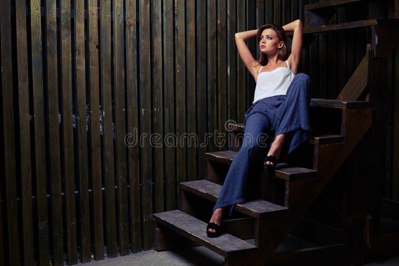 Le jeune modèle parfait regarde latéral avec des mains sur des escaliers photographie stock libre de droits