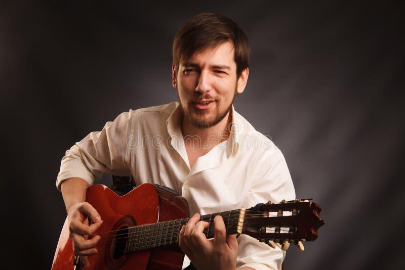 Le jeune musicien joue la guitare acoustique et chante, sur le fond foncé image stock