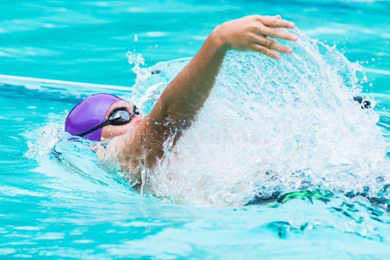 Le jeune nageur masculin nage dans la course arrière image stock