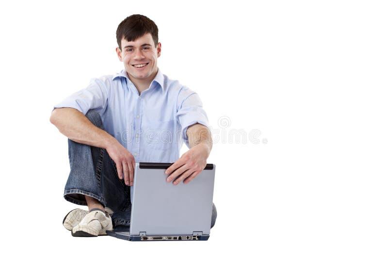 Le jeune, occasionnel homme s'asseyant sur l'étage ouvre l'ordinateur portatif photos libres de droits