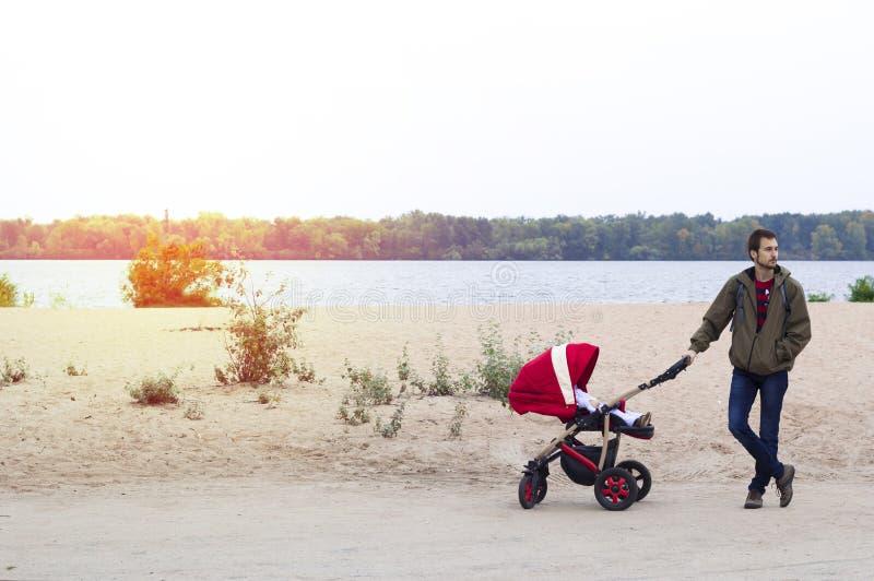 Le jeune père aide la mère, il marche avec une voiture d'enfant dans photos libres de droits