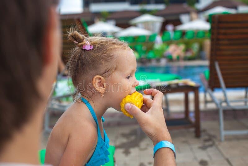 Le jeune père alimente son petit maïs de fille près photo stock