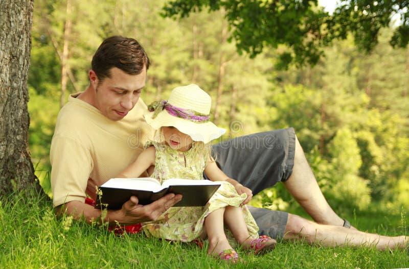 Le jeune père avec sa petite fille lit la bible photos stock