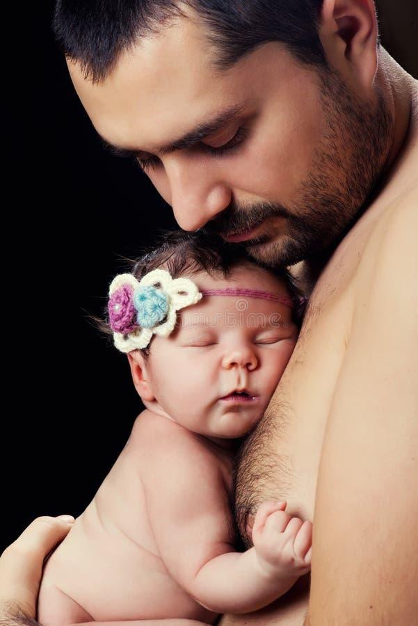 Le jeune père barbu se tient doucement sur sa fille nouveau-née de bébé de coffre images libres de droits