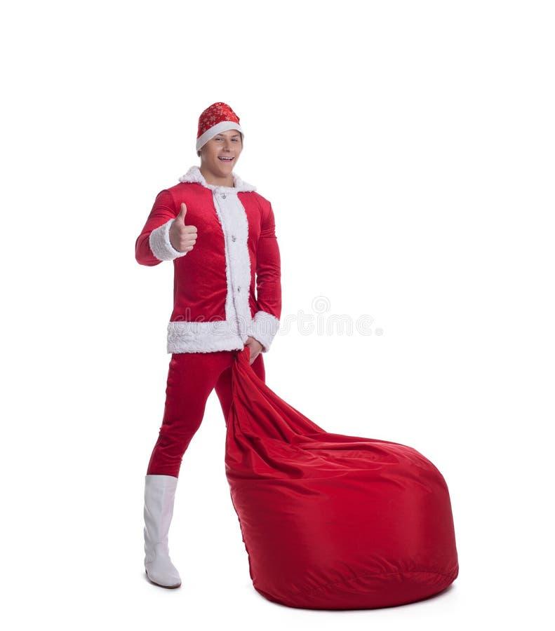 Le jeune père noël heureux avec le sac rouge énorme photos stock