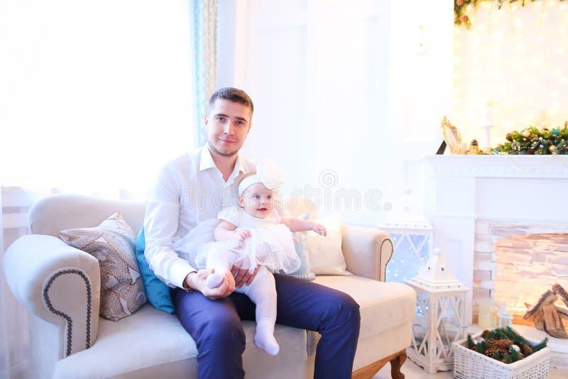 Le jeune père s'asseyant avec la fille sur le sofa près a décoré la cheminée photos libres de droits