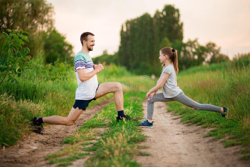 Le jeune père sportif et peu de fille font des exercices Style de vie sain photo libre de droits