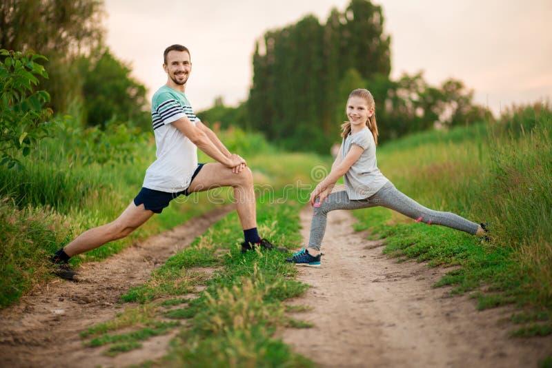 Le jeune père sportif et peu de fille font des exercices Style de vie sain photographie stock libre de droits