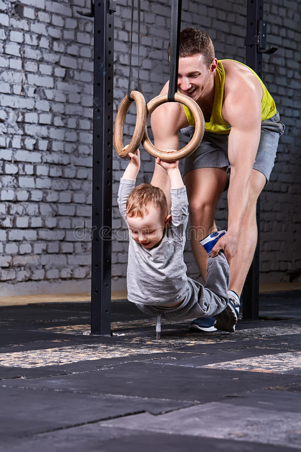 Le jeune père sportif forme le petit fils avec les anneaux gymnastiques contre le mur de briques au gymnase convenable de croix photographie stock