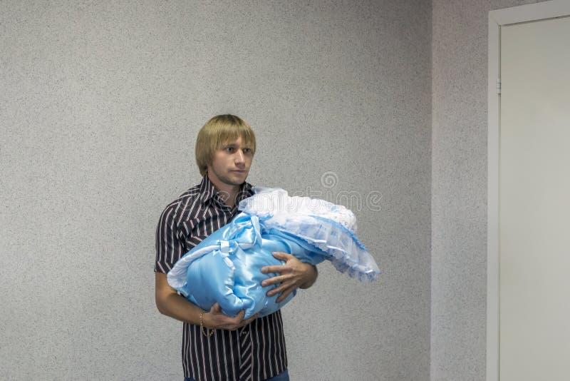 Le jeune père tient un paquet avec son nouveau-né à l'hôpital de naissance images stock