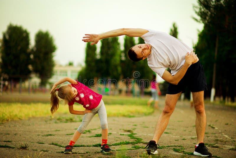 Le jeune p?re sportif et la petite fille font des exercices dans le stade photos stock