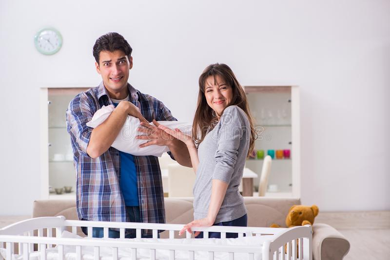 Le jeune parents avec leur bébé nouveau-né près du berceau de lit photo libre de droits