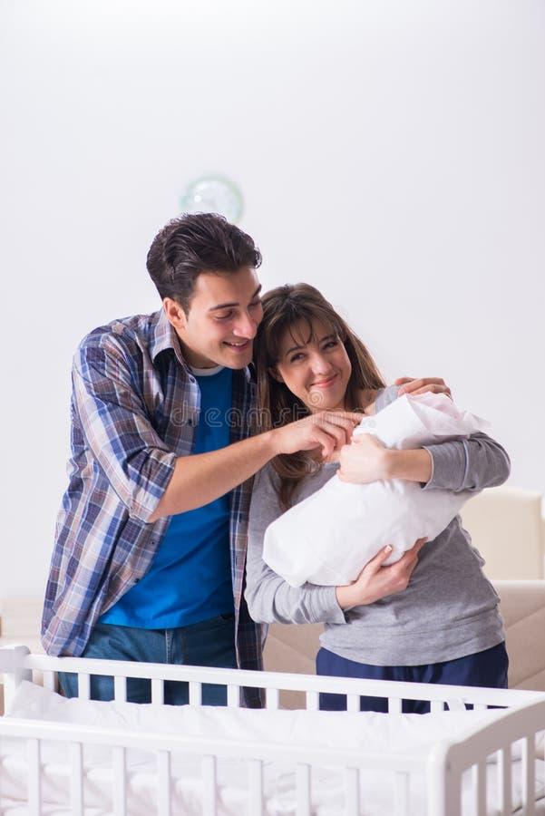 Le jeune parents avec leur bébé nouveau-né près du berceau de lit image stock