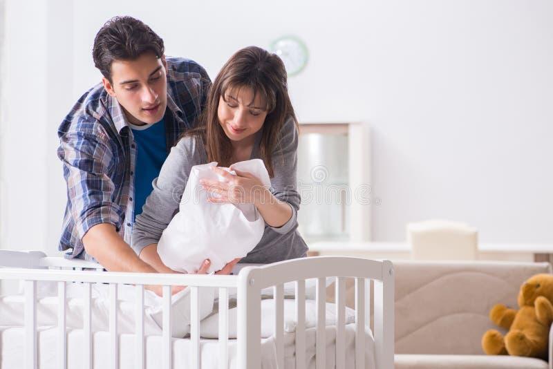 Le jeune parents avec leur bébé nouveau-né près du berceau de lit images stock