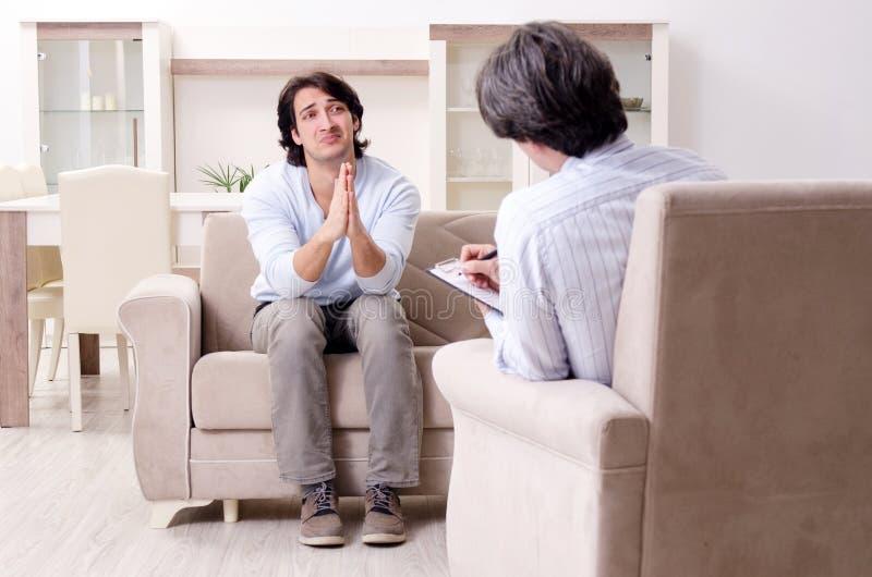 Le jeune patient masculin discutant avec des probl?mes personnels de psychologue image libre de droits