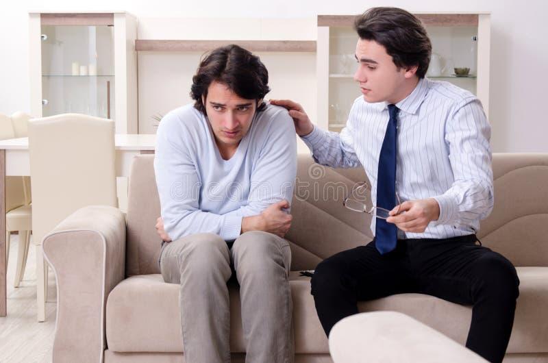 Le jeune patient masculin discutant avec des probl?mes personnels de psychologue photographie stock