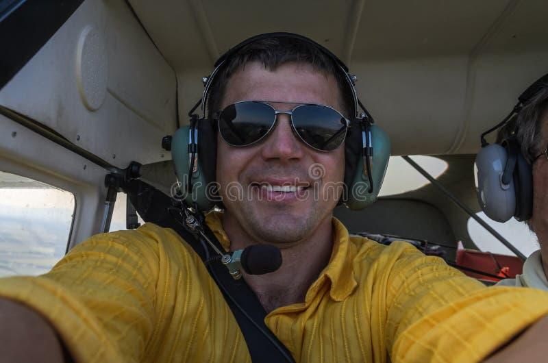 Le jeune pilote dans les verres et des écouteurs fait le selfie dans un avion dans la cabine du pilote images libres de droits