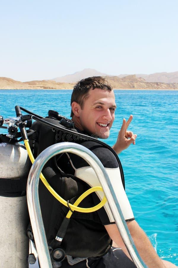Le jeune plongeur heureux dans un costume pour plonger dispose à plonger images stock