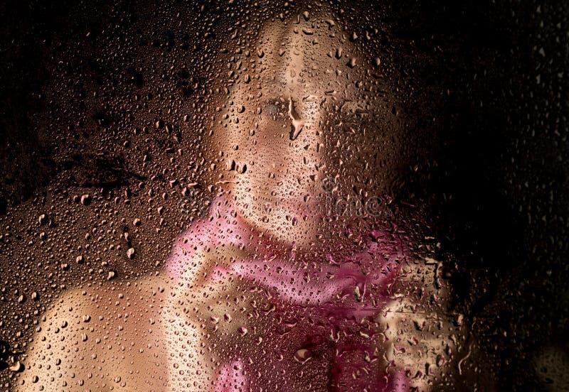 Le jeune portrait triste de femme derrière la fenêtre sous la pluie avec la pluie se laisse tomber là-dessus images libres de droits