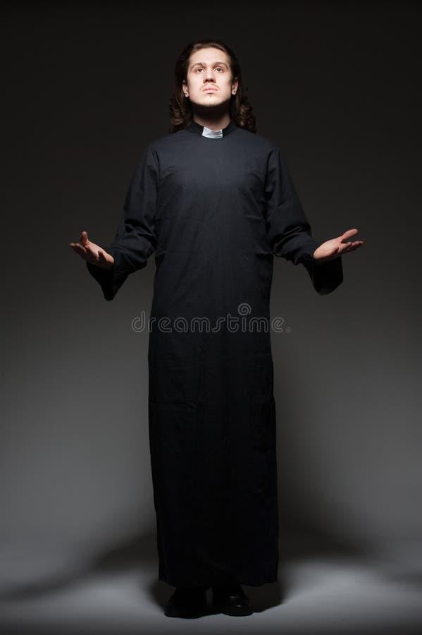 Le jeune prêtre prie images stock