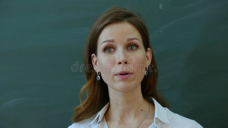 Le jeune professeur féminin disent intéressant pour classer près du tableau noir images stock