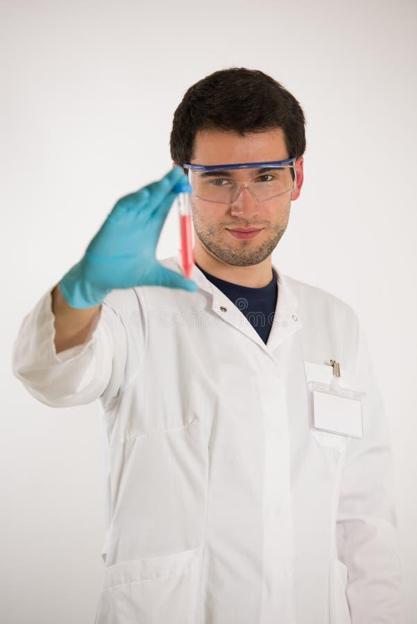 Le jeune scientifique tient des tubes image stock