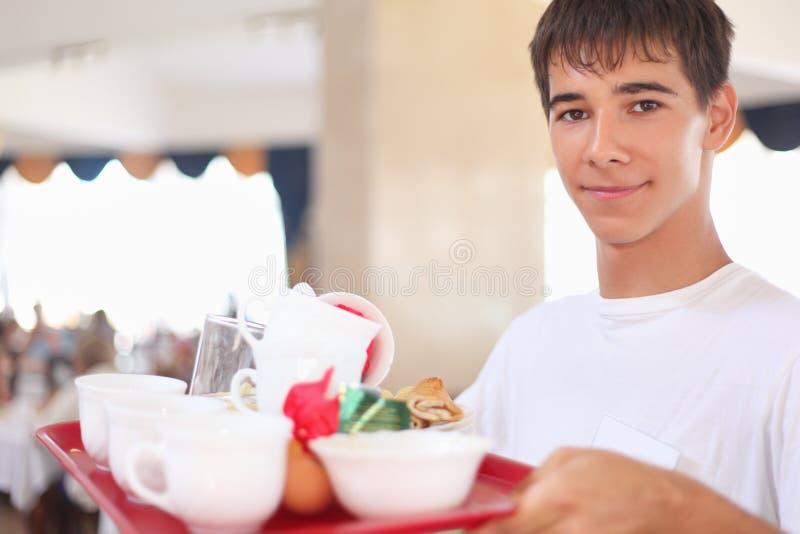 Le jeune serveur affable garde le plateau au restaurant photos stock