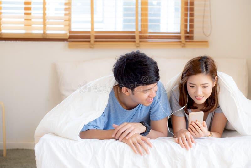 Le jeune sourire asiatique de couples écoutent musique avec le téléphone portable intelligent sur le lit à la chambre à coucher a images stock